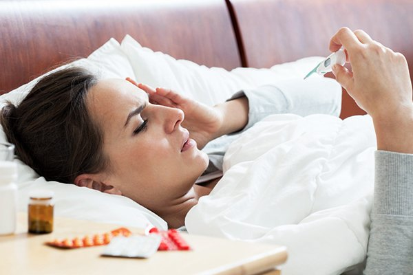 A woman sick lying in bed with a cold