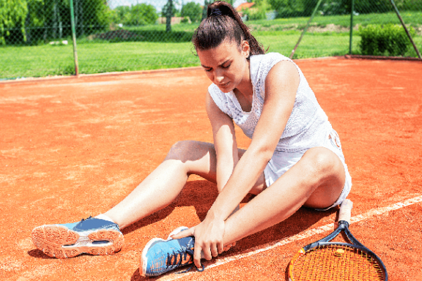 Tennis player holding her hurt ankle