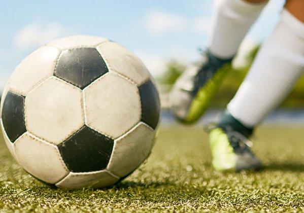Closeup of kid kicking a soccer ball