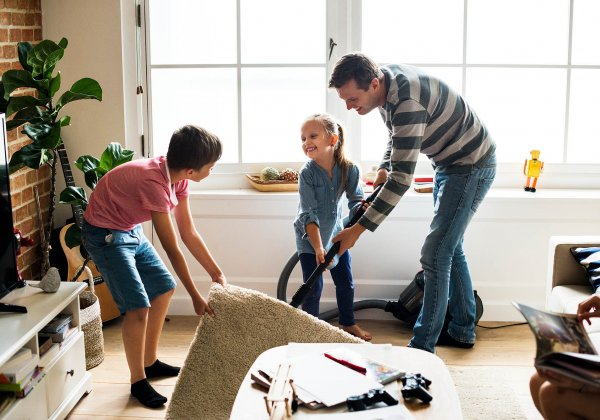 Father and Children Vacuuming Floor