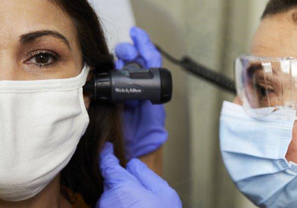 Nurse checking patients ear