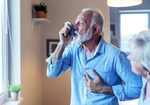 Older man with asthma using inhaler