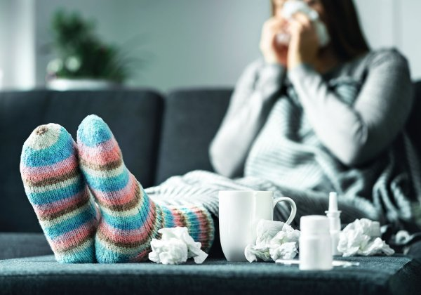 Woman blowing nose on the couch