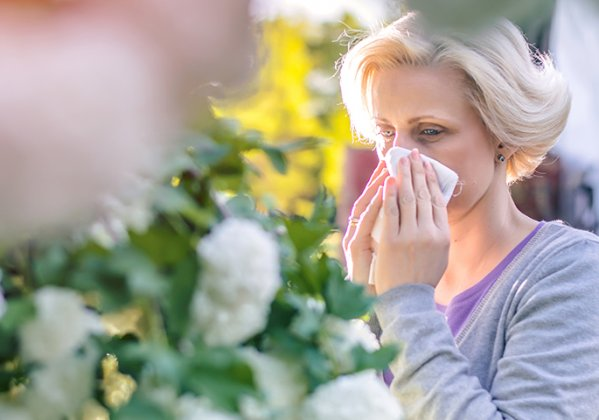 Woman sneezing outside among blooming trees