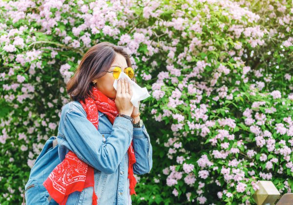 Woman with allergies blowing her nose while outside